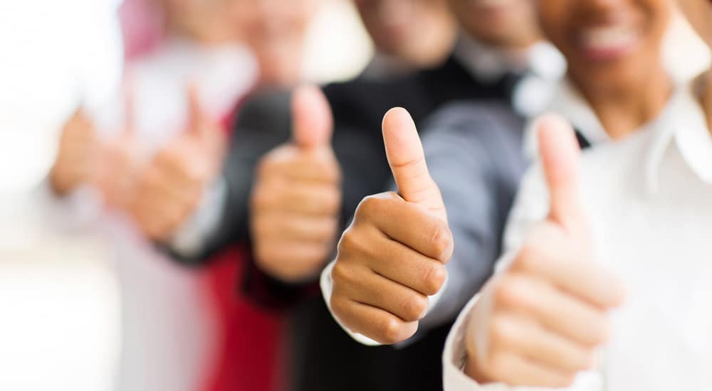 Multiple businesspeople lined up and giving thumbs up