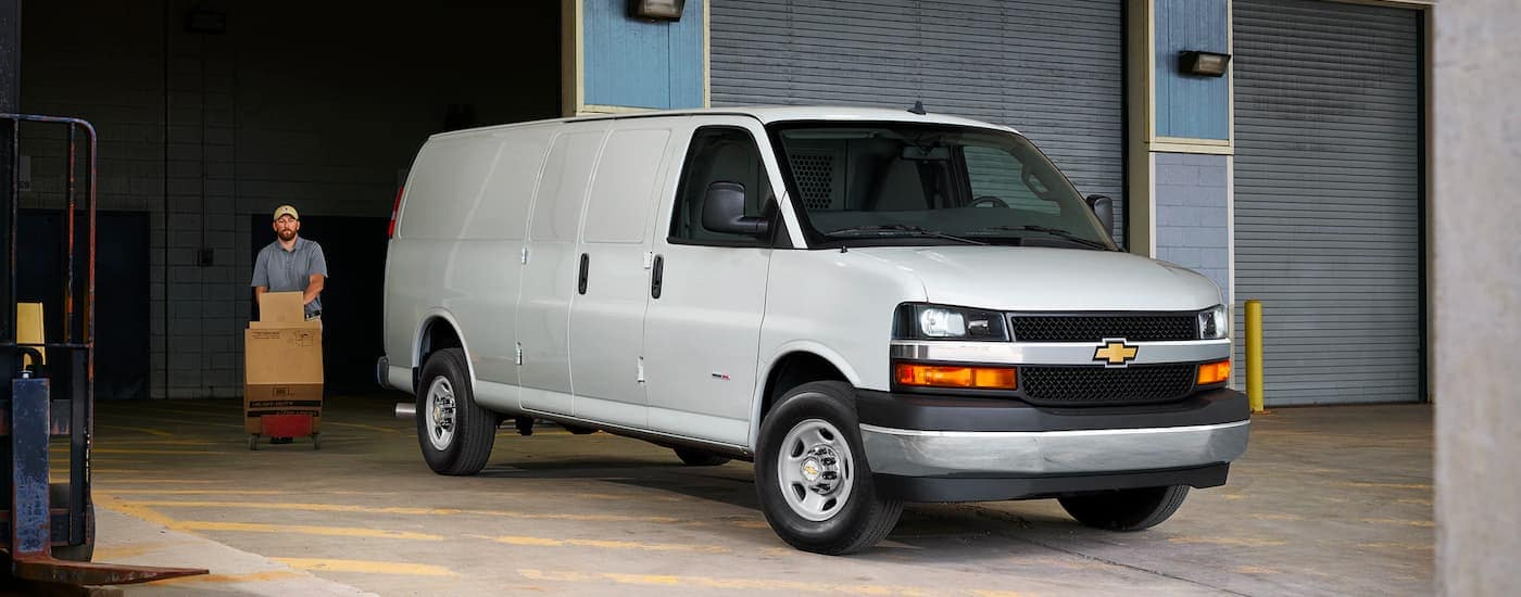 A white 2021 Chevy Express is shown on a loading dock with a delivery man who has a dolly full of cardboard boxes.