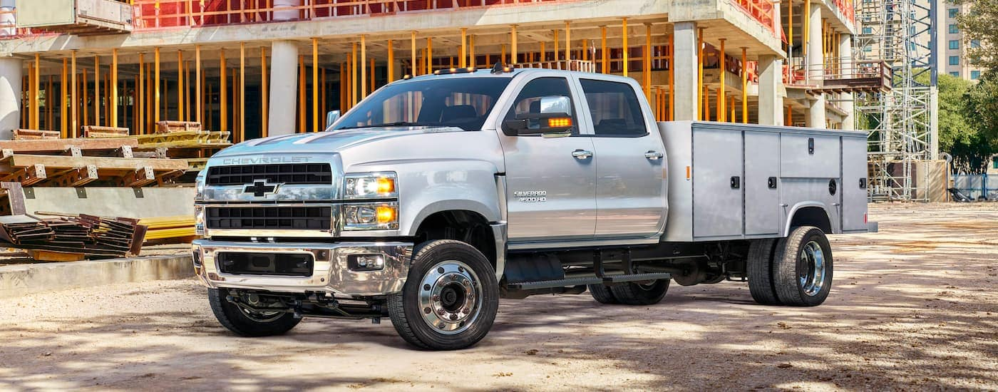 A silver 2021 Chevy Silverado 4500 HD is shown angled left, parked with a building being constructed in the background.