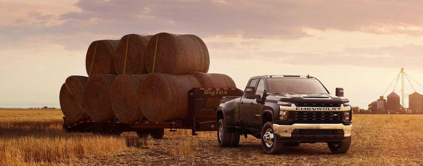 A black 2021 Chevy Silverado HD 3500 LT is shown parked in a field with large hay bales on a gooseneck trailer