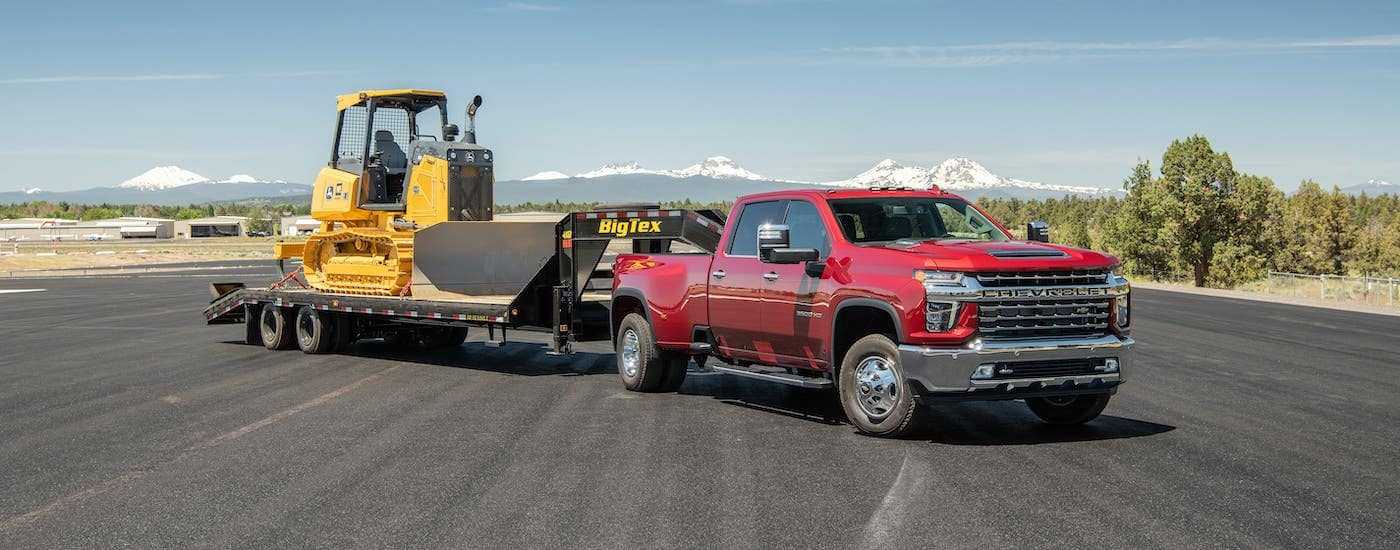 A red 2021 Chevy Silverado 3500HD is towing construction equipment in front of distant snow-covered mountains.
