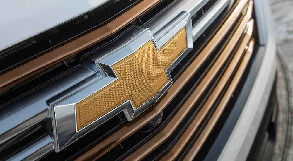A closeup shows the gold bowtie badging on the grille of a 2022 Chevy Traverse at an Albany Chevy dealership.
