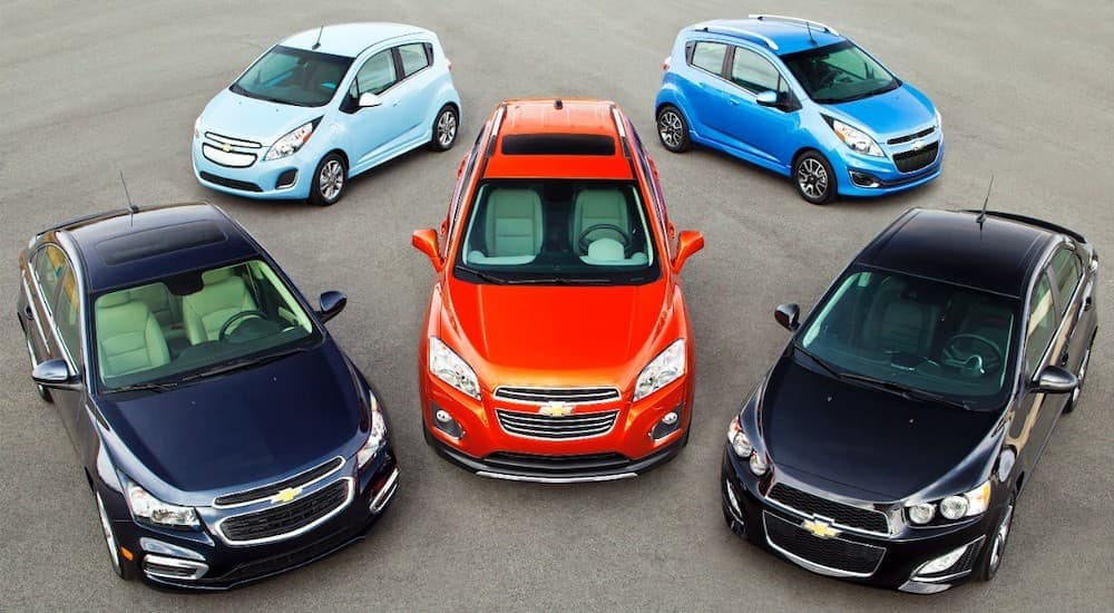 Five Chevy cars from 2014 are parked in an open area at an Albany used car dealership.