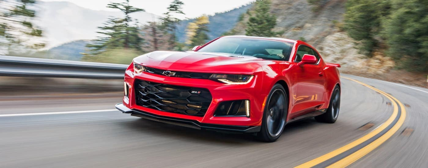 A red 2018 Chevy Camaro ZL1 is shown driving down a mountain road.