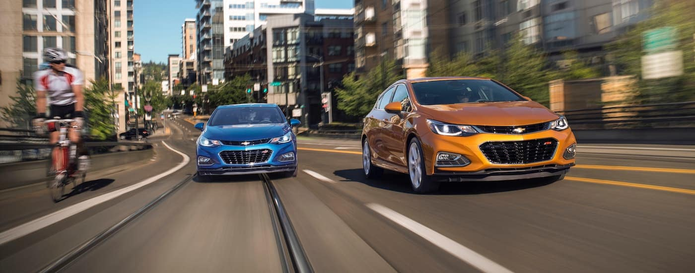 A blue and an orange 2018 Chevy Cruze are diving on a multi-lane road through a city.