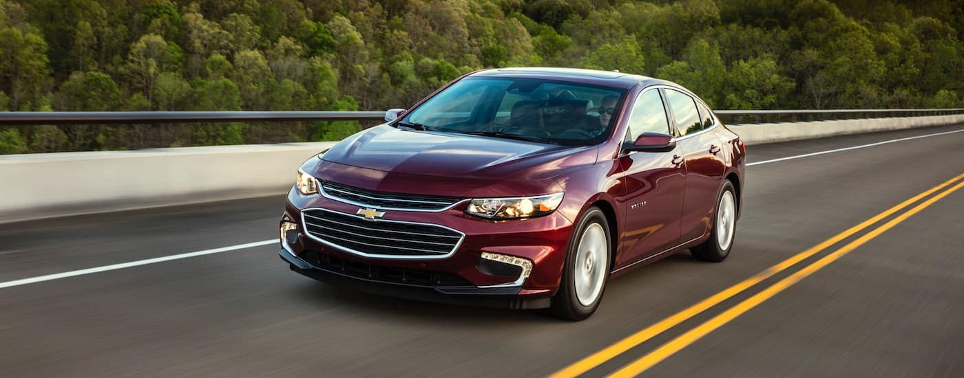 A burgundy 2018 Chevy Malibu is driving on a highway.