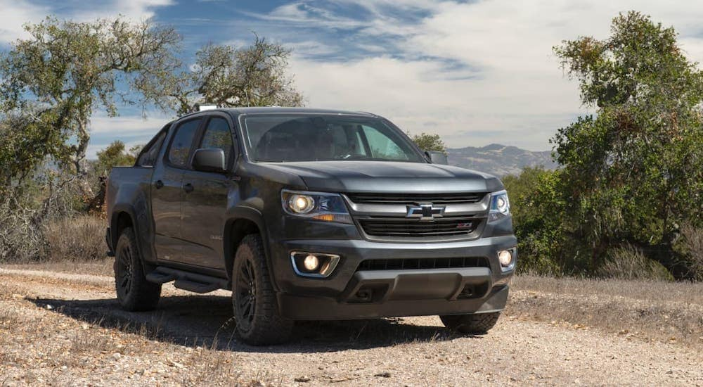 A black 2016 Chevy Colorado is parked on a dirt trail after leaving a used car dealer in Albany.