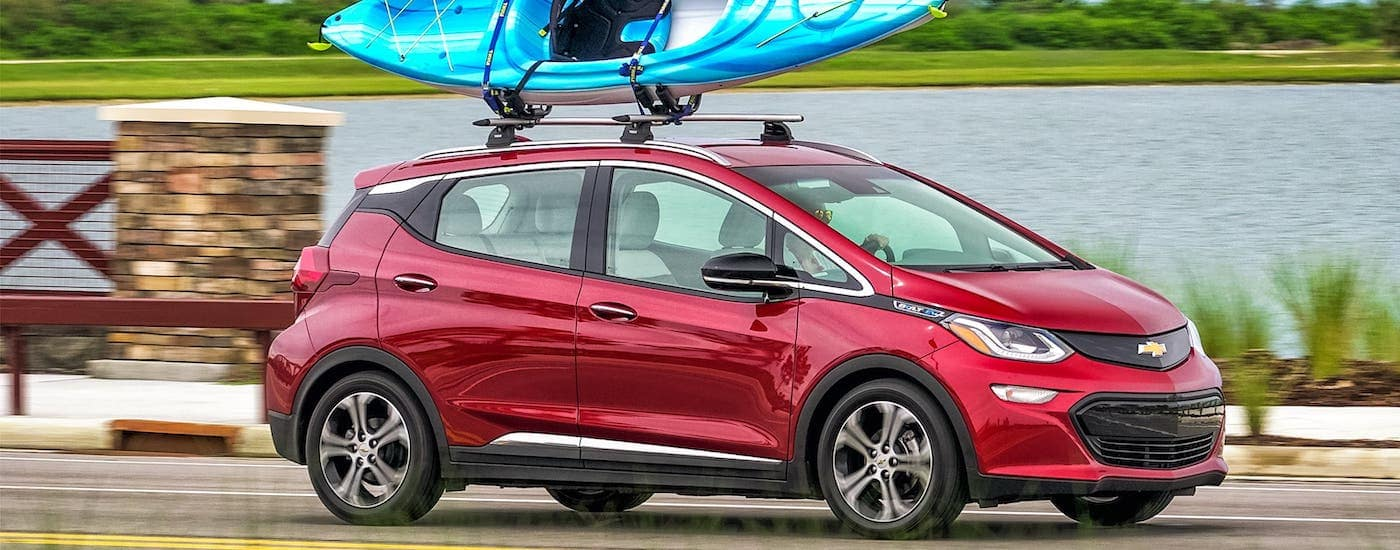 A red 2018 Chevy Bolt EV with a kayak on the roof is driving past a river.