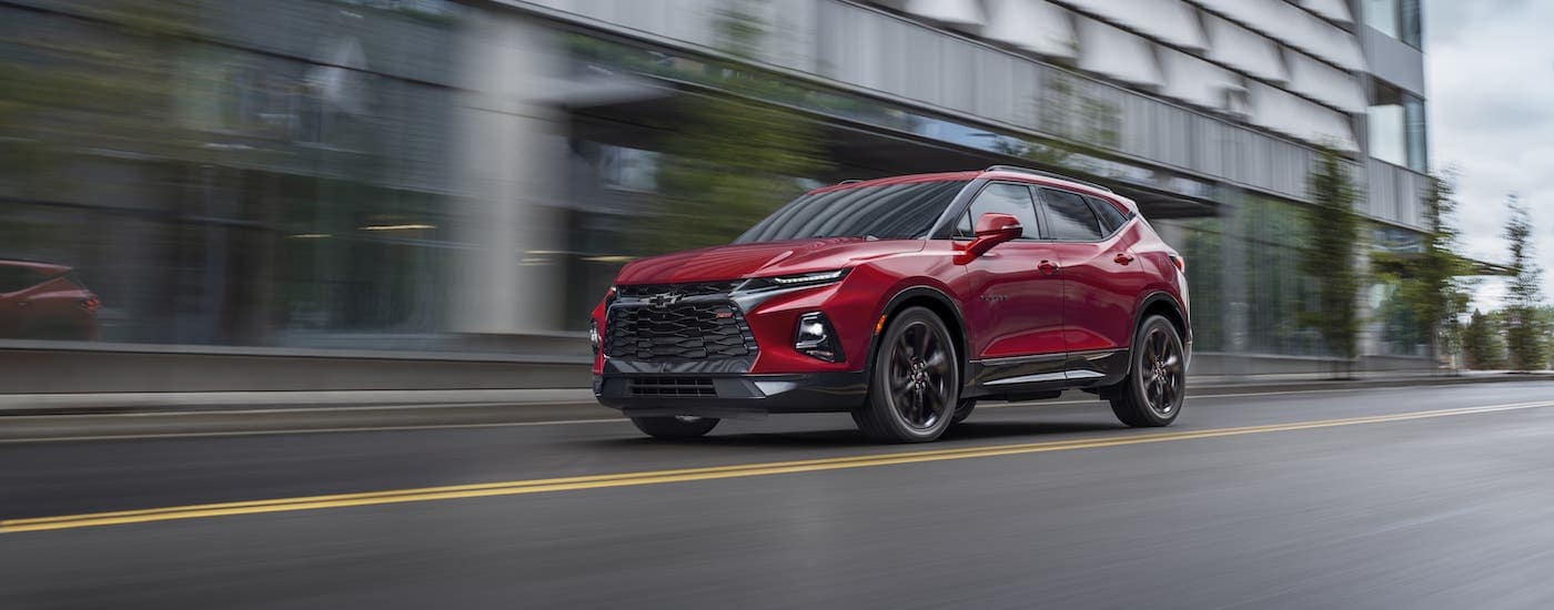 A red 2019 Chevy Blazer RS is driving on a city street.