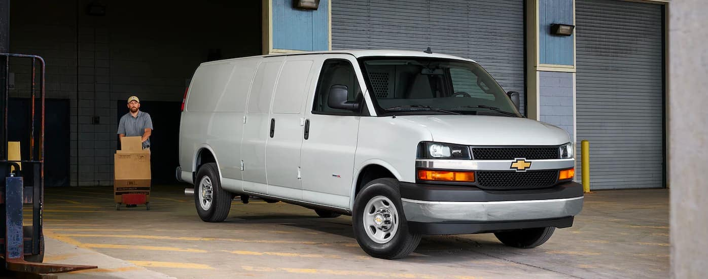 A white 2021 Chevy Express 3500 is parked outside of a warehouse with a delivery person loading boxes.