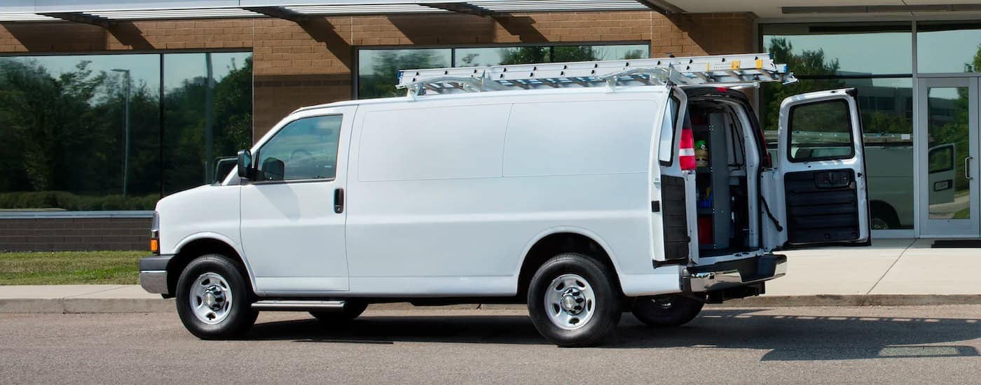 A white 2021 Chevy Express 3500 is shown from the side with the rear doors open.