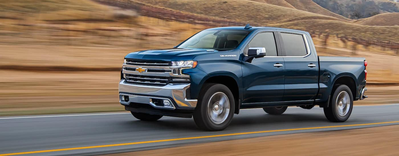 A blue 2021 Chevy Silverado 1500 is speeding past a field with yellow grass.