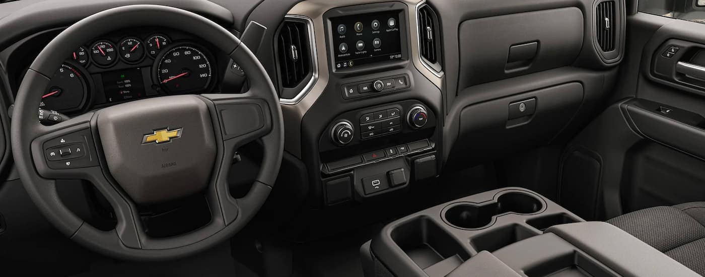 The black interior and infotainment screen is shown on a 2021 Chevy Silverado 3500 HD Chassis Cab.