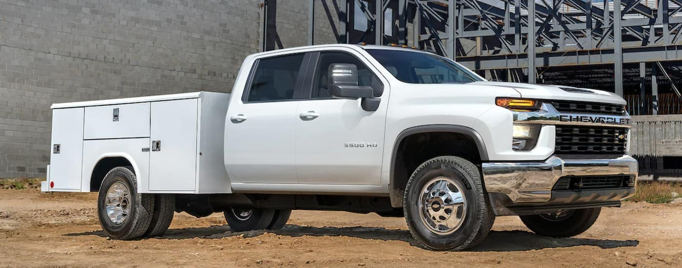A white 2021 Chevy Silverado 3500 HD Chassis Cab is parked in front of a cinder block wall.