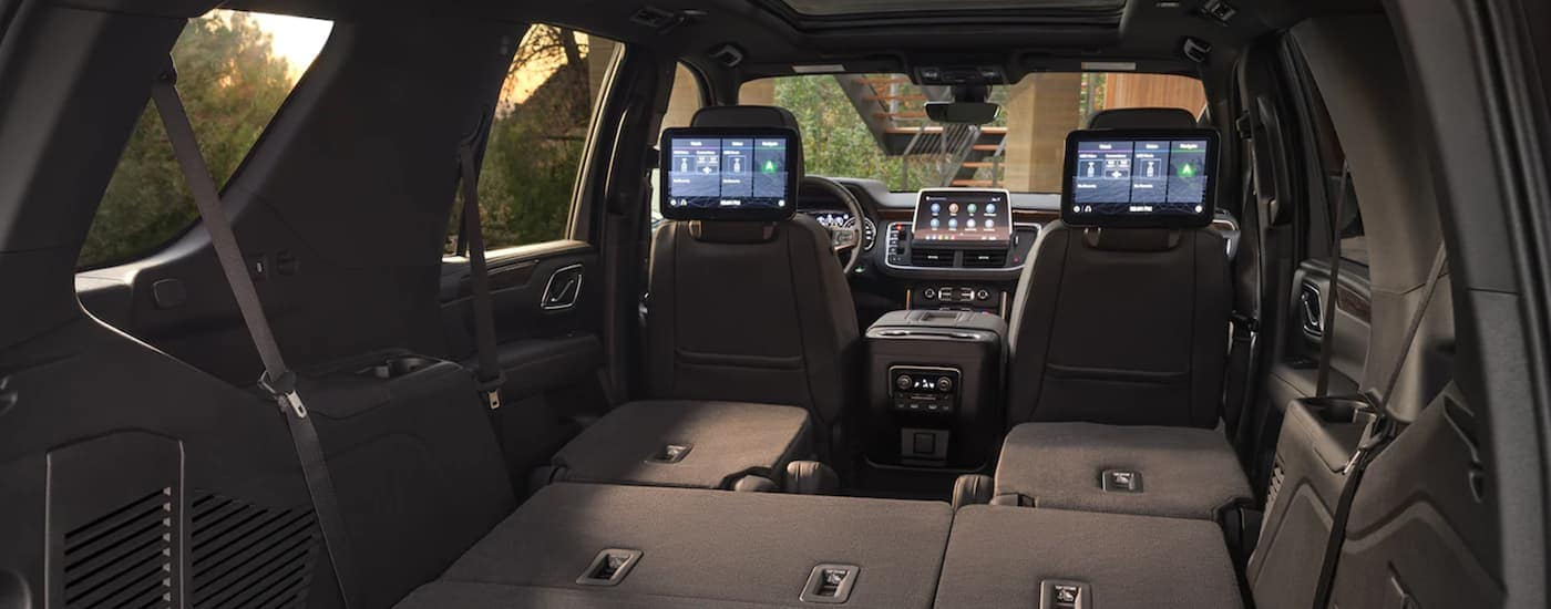 The black interior, headrest screens, and infotainment screen is shown on a 2021 Chevy Tahoe.