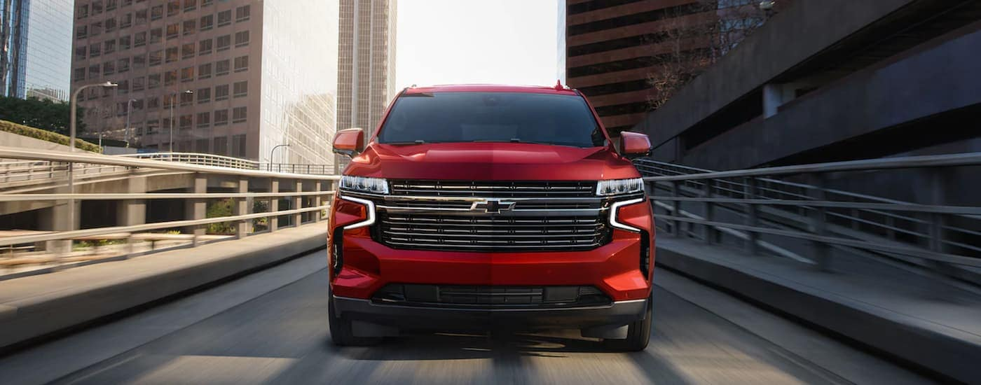 A red 2021 Chevy Tahoe is shown from the front driving down an off ramp.