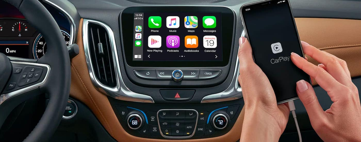 A close up shows a person using Apple CarPlay on the infotainment screen of a 2021 Chevy Equinox.