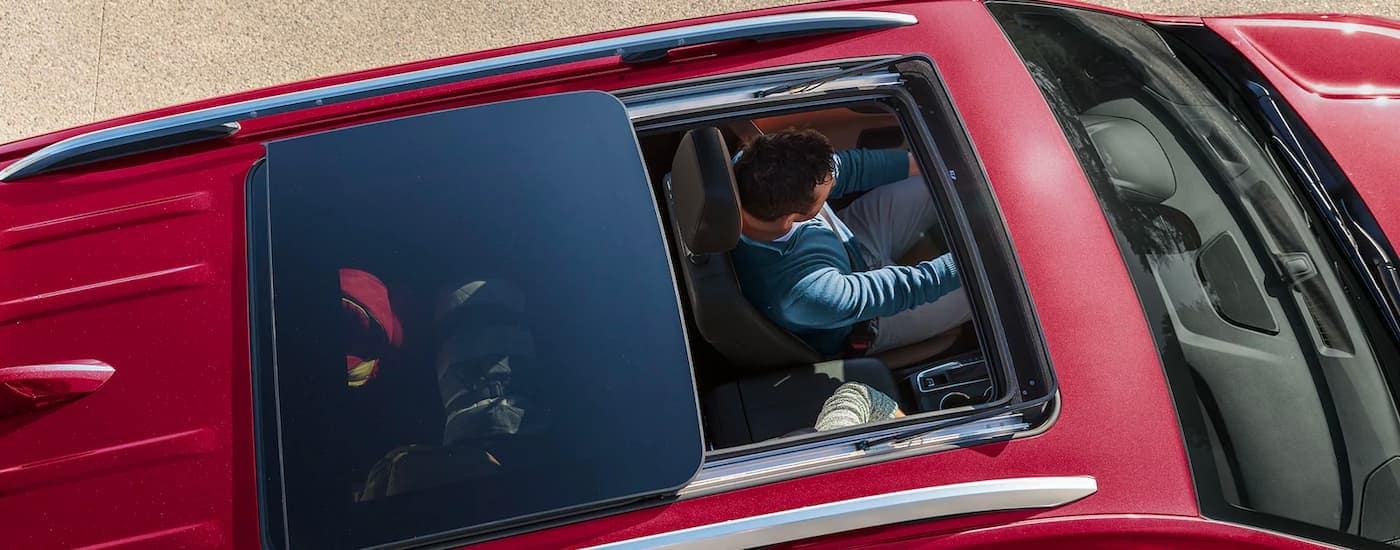 A close up shows a driver from a high angle, through moonroof of a red 2021 Chevy Equinox.
