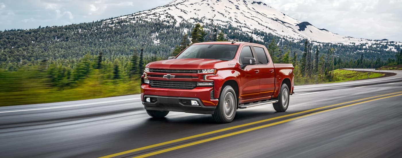 A red 2021 Chevy Silverado 1500 is shown driving past snowy distant mountains after winning the 2021 Chevy Silverado 1500 vs 2021 Ram 1500 comparison.