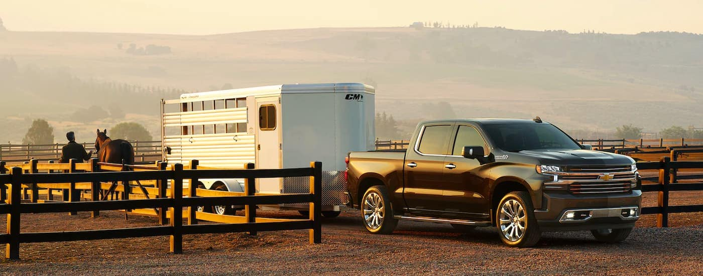 A black 2021 Chevy Silverado 1500 is shown parked near a fence while towing a silver horse trailer.