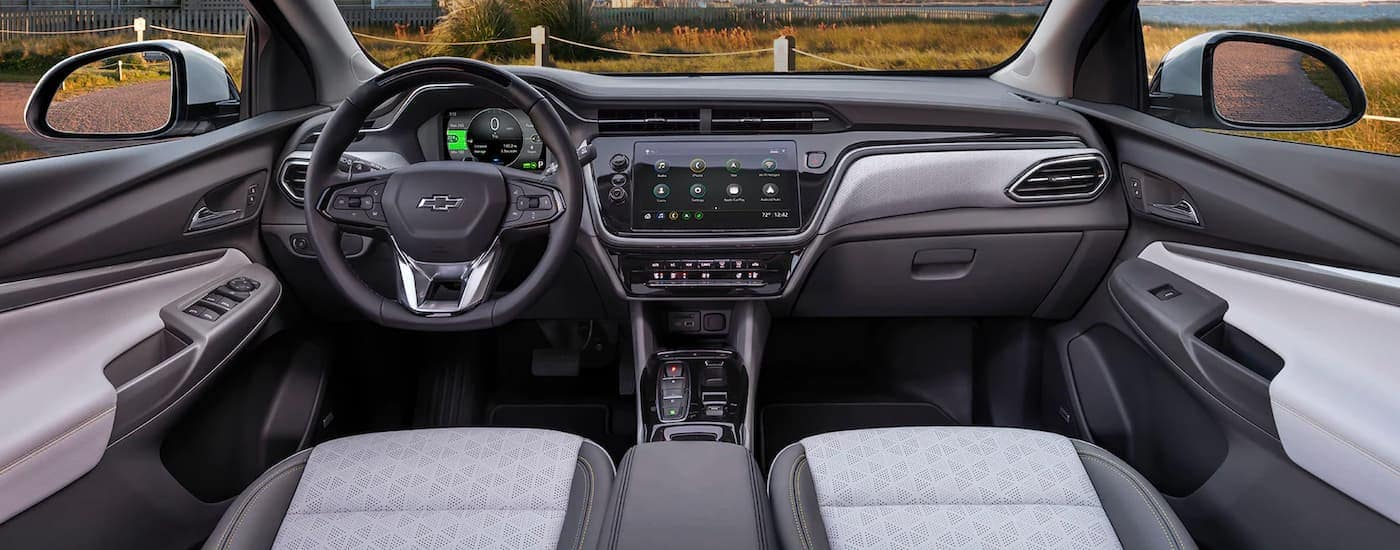 The black and gray front interior seats and dash are shown in a 2022 Chevy Bolt EUV.