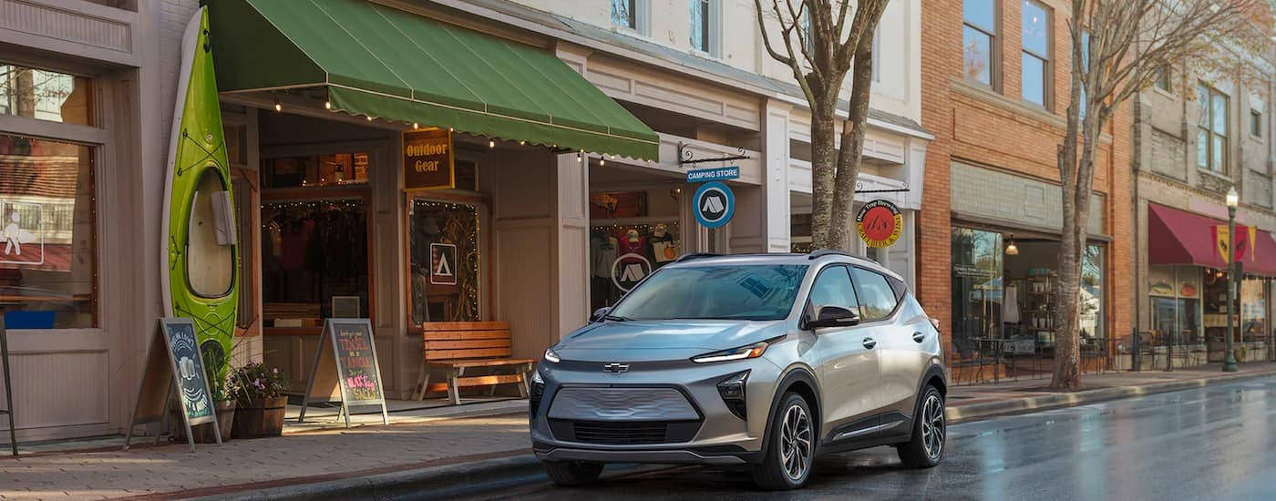 A silver 2022 Chevy Bolt EUV is shown parked in front of and outdoor shop.