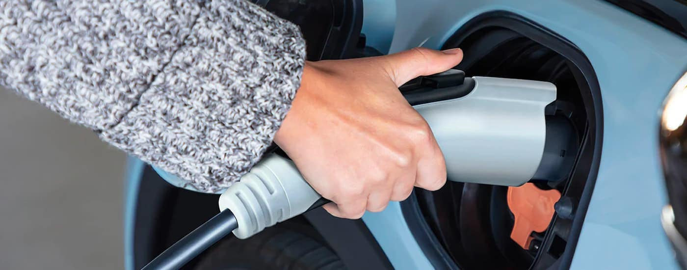 A close up shows a charging cable being plugged in to a pale blue 2022 Chevy Bolt EV.