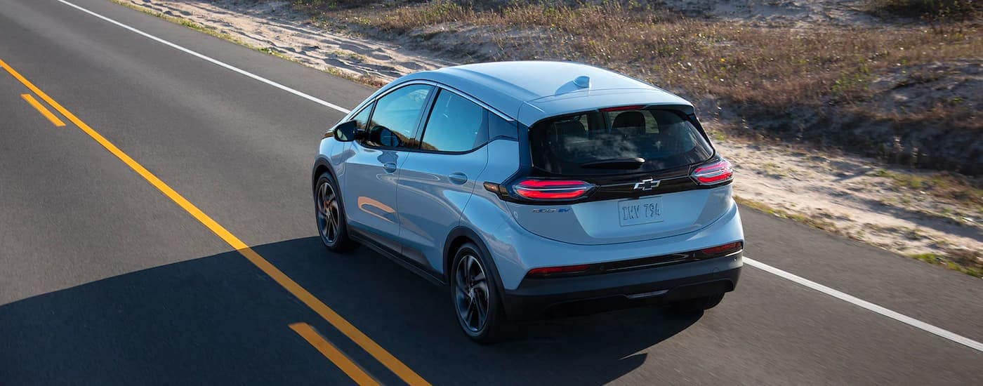 A silver 2022 Chevy Bolt EV is shown from the rear driving down and empty road.