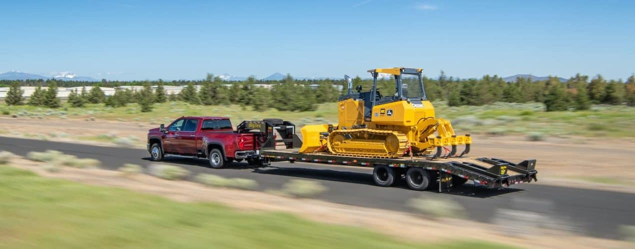 A red 2021 Chevy Silverado 3500 HD is towing construction equipment past a field.