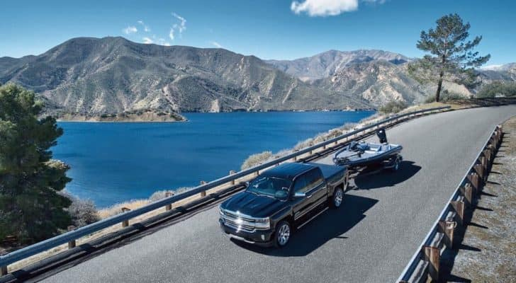 A black 2018 Chevy Silverado 1500 High Country is shown from a high angle towing a boat over a road next to lake.