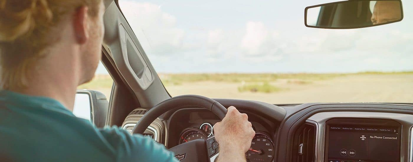 A person is shown driving a 2020 Chevy Silverado 1500 LT Z71 Trail Boss.