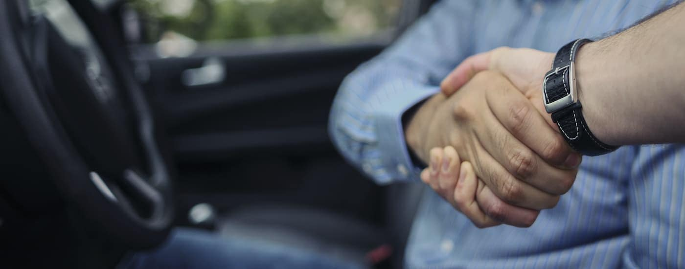 A salesman is shaking the hand of someone in the front seat of a car.