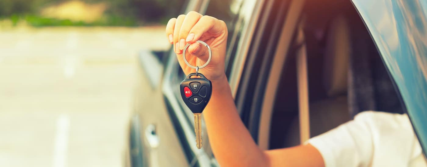 A person is holding a set of keys out the window of a used car.