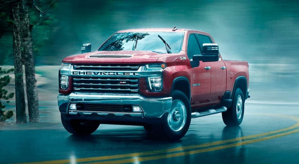 A red 2021 Chevy Silverado 2500 HD is shown rounding a corner in the rain after leaving a Chevrolet Silverado HD dealer.
