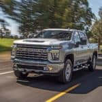 A silver 2021 Chevy Silverado 2500 HD Z71 is shown driving down a tree lined road.