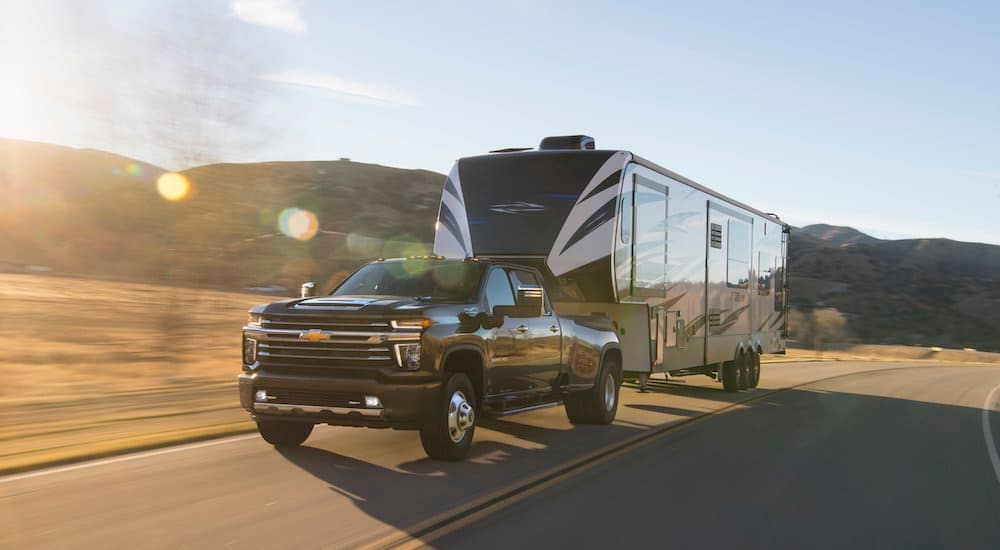 A black 2021 Chevy Silverado 3500 HD is shown towing a trailer down a sunny road.