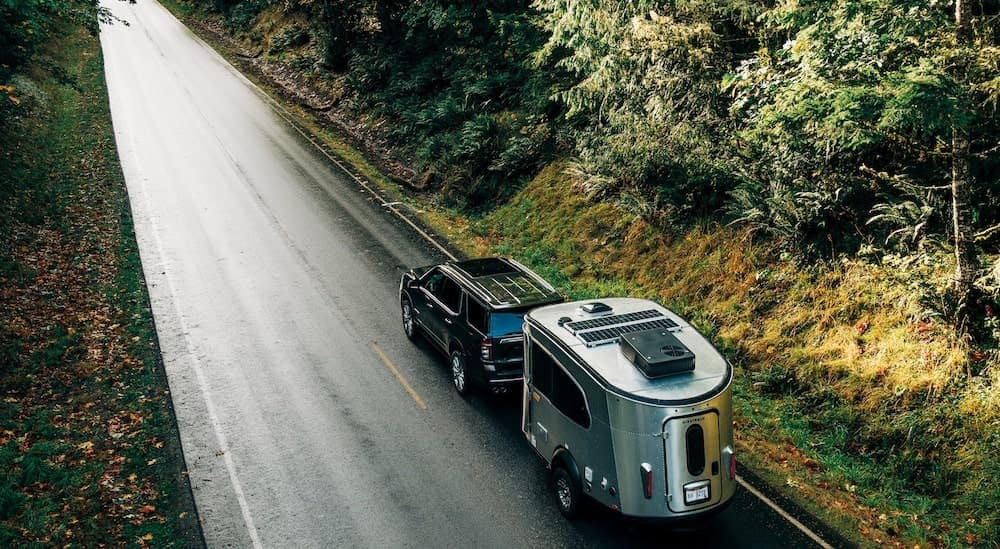 a black 2021 Chevy Tahoe High Country is shown from a high angle towing and Airstream trailer down a wooded road.