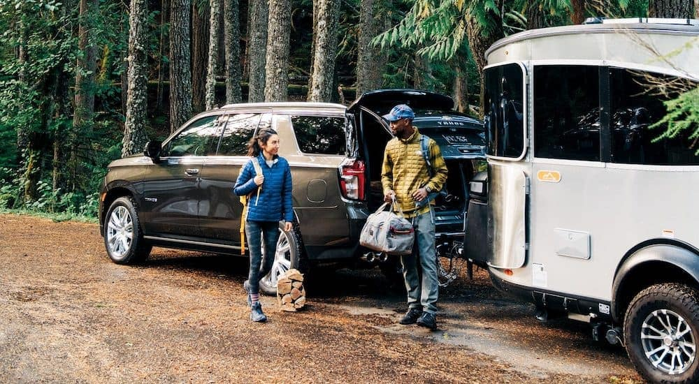 People are shown standing next to a 2021 Chevy Tahoe High Country and an Airstream trailer.