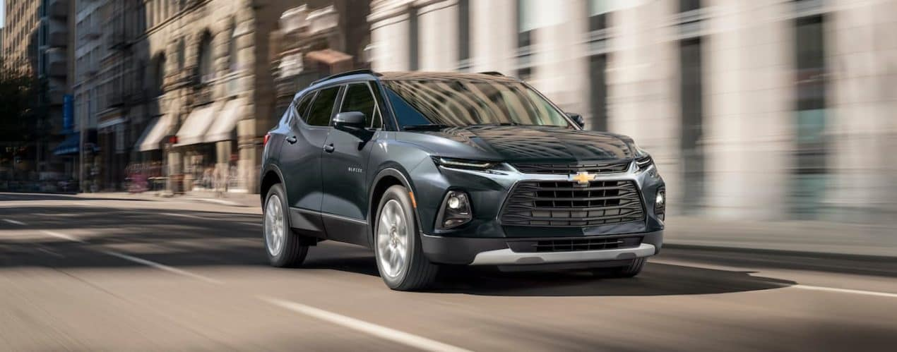 A grey 2022 Chevy Blazer vs 2021 Nissan Murano is show driving through a city after winning a 2022 Chevy Blazer vs 2021 Nissan Murano comparison.
