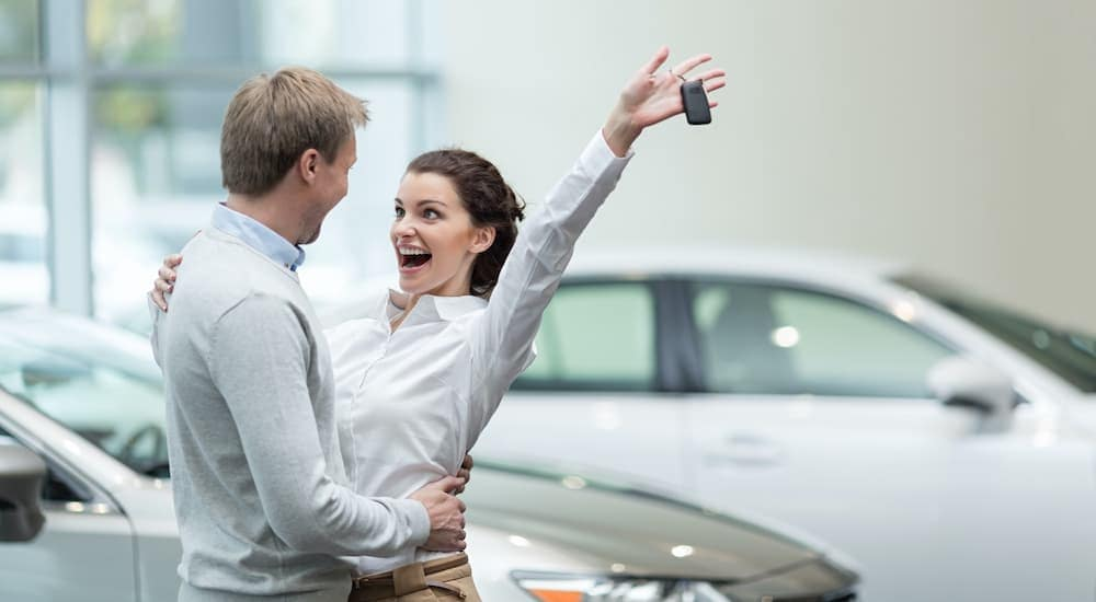 A couple is excited while a woman holds up a set of car keys.