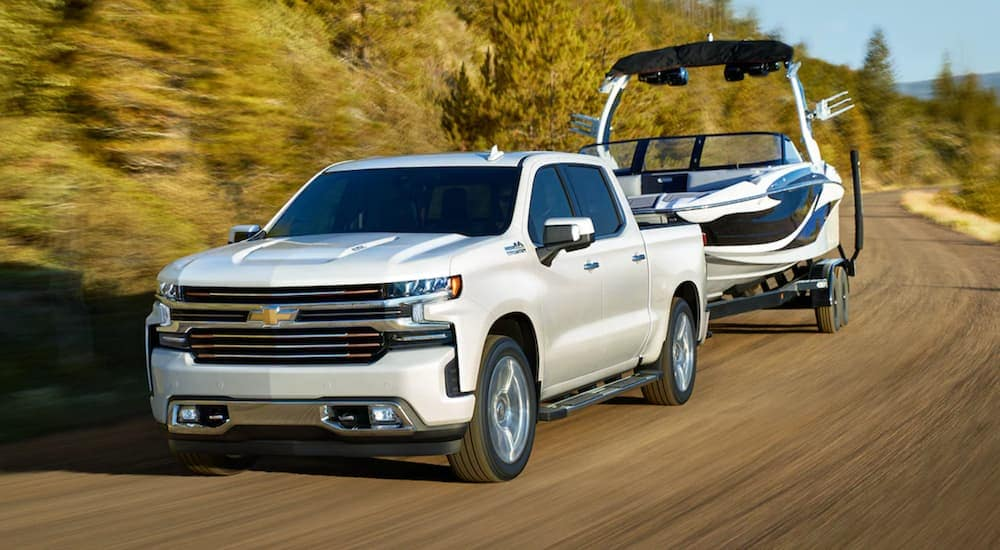 A white 2021 Chevy Silverado 1500 is towing a boat after leaving a Chevy 1500 diesel dealer.