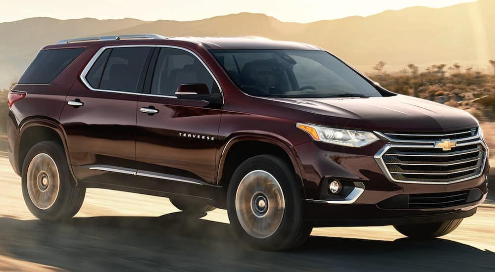 A maroon 2021 Chevy Traverse is shown driving on an open road past a desert.