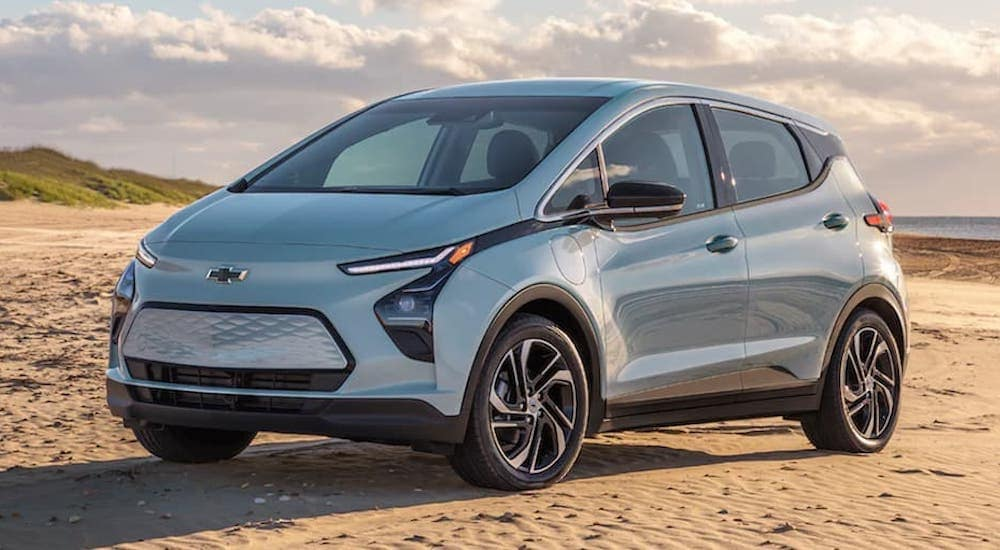 A light blue 2022 Chevy Bolt EV is shown from an angle parked on the beach.