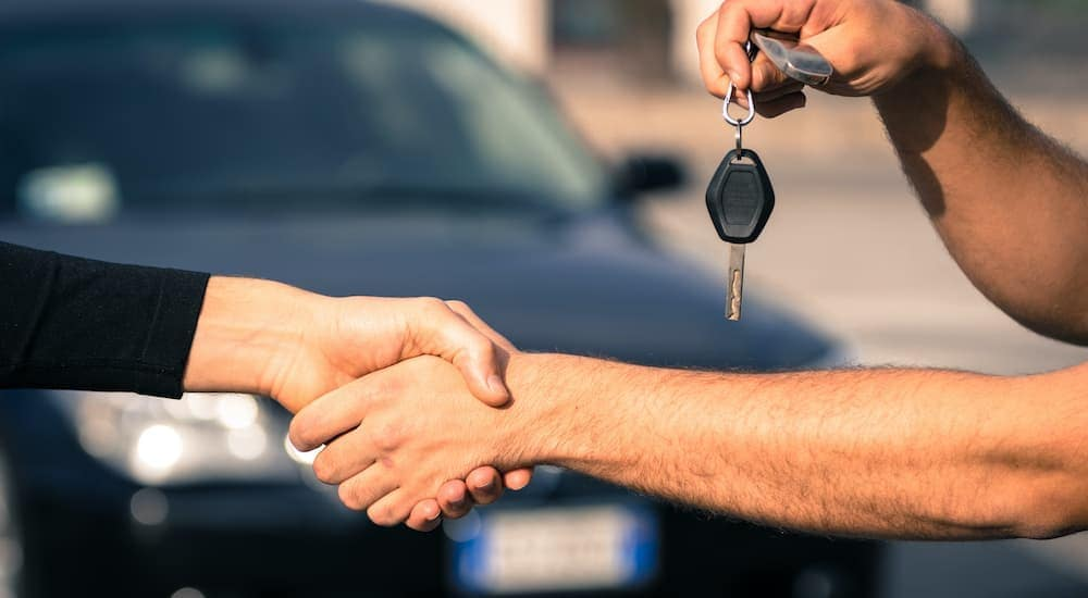 A salesman is shaking hands with a car buyer at an Albany used car dealership.