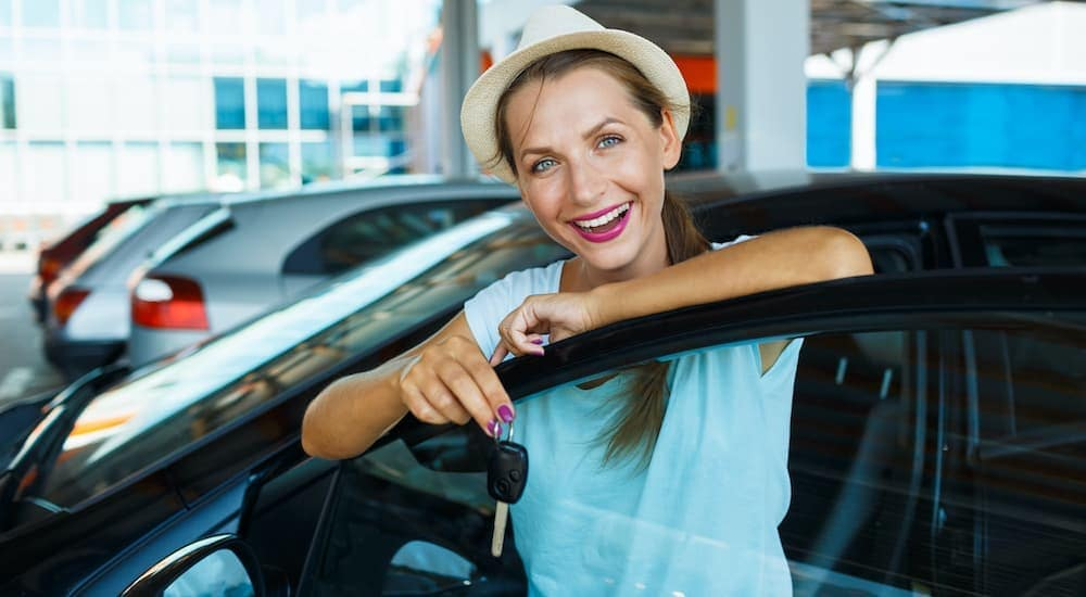 A woman is shown holding a set of keys at an Albany used car dealership.
