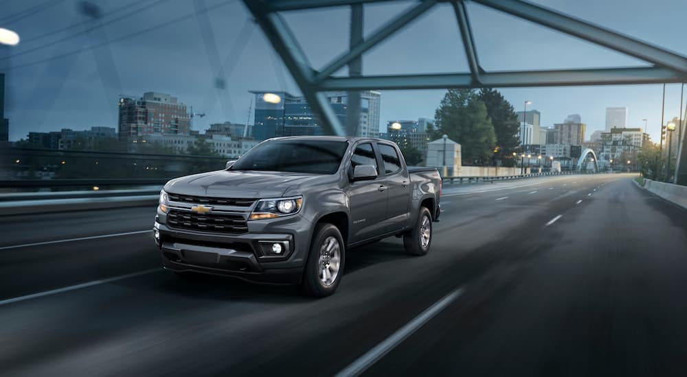 A grey 2022 Chevy Colorado LT is shown driving over a bridge at night.