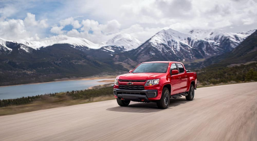 A red 2022 Chevy Colorado Trailboss is shown driving through the mountains after visiting a Chevrolet truck dealership.