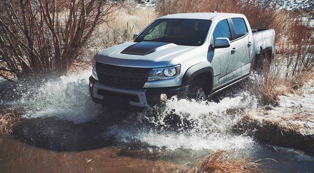 A silver 2022 Chevy Colorado ZR2 Bison is shown splashing through water.