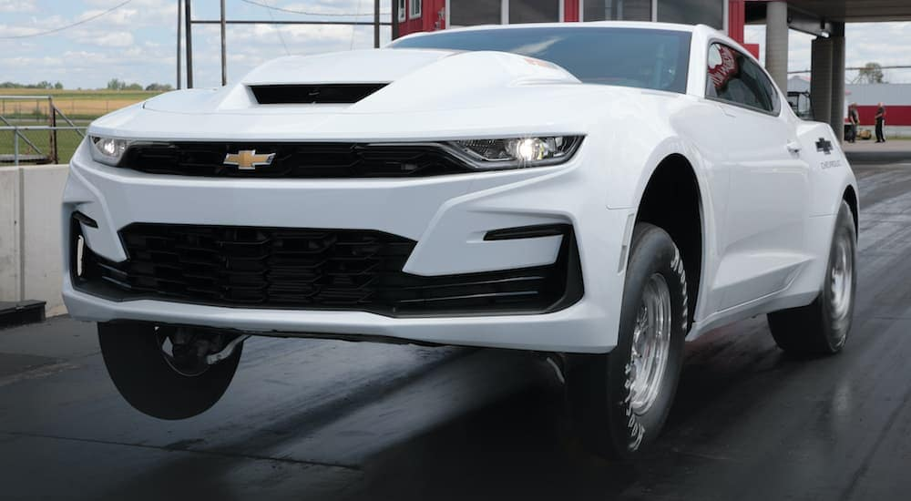 A white 2022 Chevy COPO Camaro is shown doing a wheelie at the drag strip after leaving one of the most popular Chevy dealers in NY.