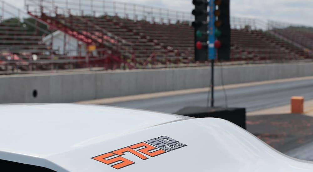 The white hood and badging is shown on a 2022 Chevy COPO Camaro at the staging area at a drag strip.